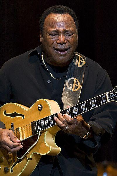 George Benson playing guitar on stage