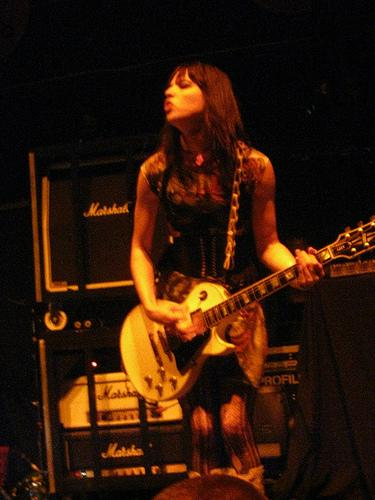 Lzzy playing guitar on stage with Halestorm
