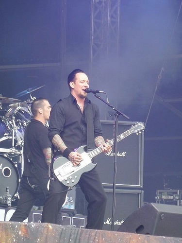 Michael Poulsen playing guitar with Volbeat