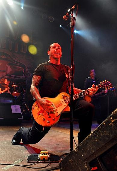 Mike Ness playing guitar live on stage
