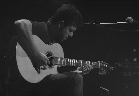 Rodrigo playing acoustic guitar on stage