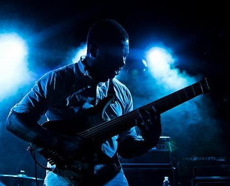 Tosin Abasi playing guitar at concert
